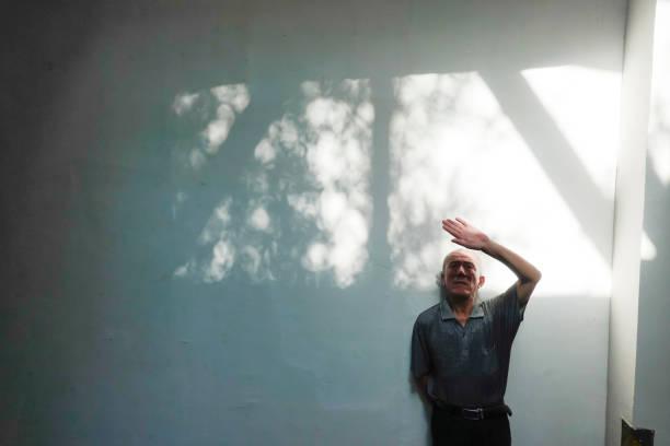 anciano de pie frente a la pared blanca con sombra - foto de stock