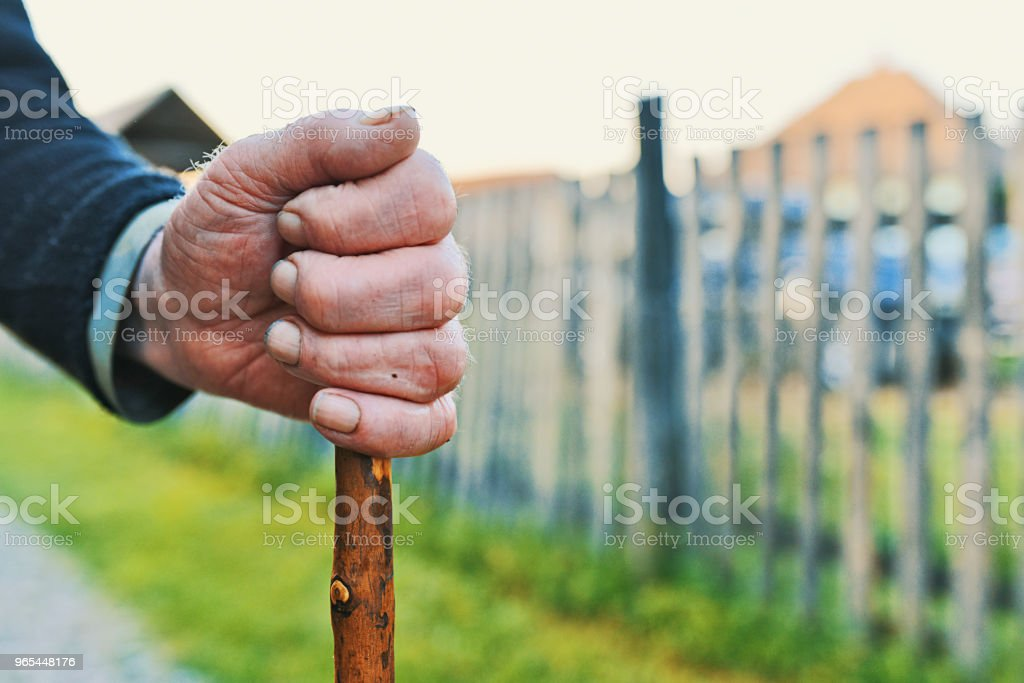 Old man standing with his wooden walking stick royalty-free stock photo