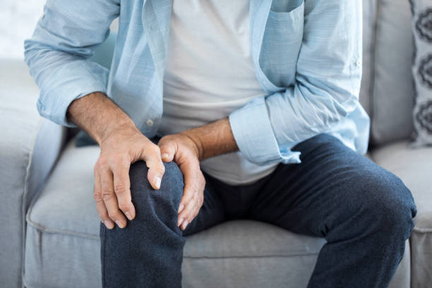 Old man suffering from knee pain stock photo