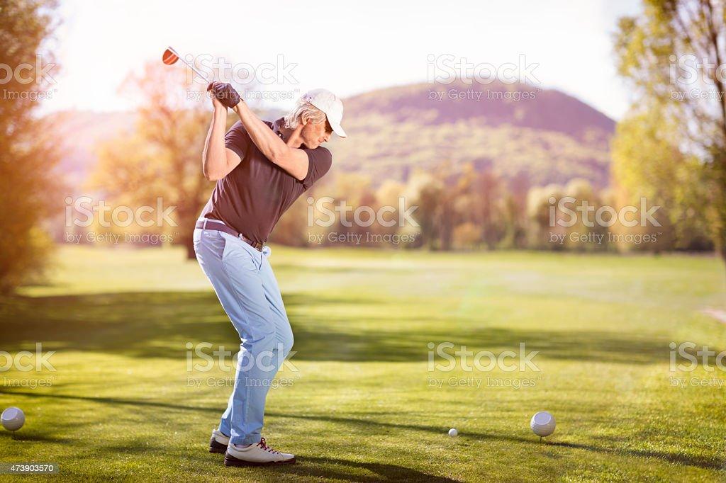 Old man swinging golf club. stock photo