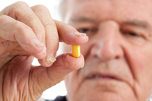 Old man taking a pill. stock photo