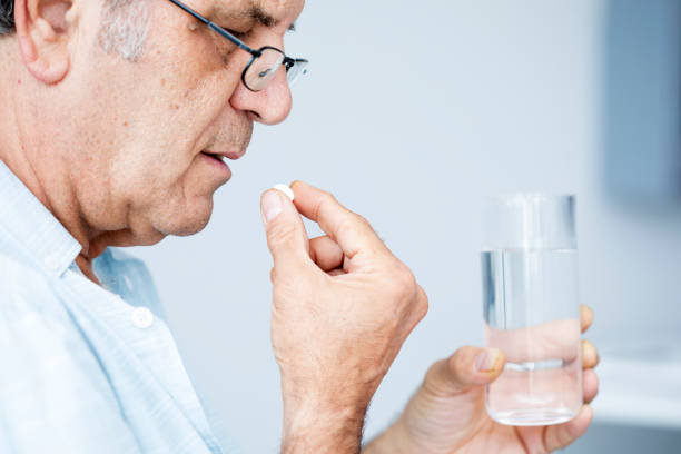 Old man taking a pill Old man taking a pill using mouth stock pictures, royalty-free photos & images