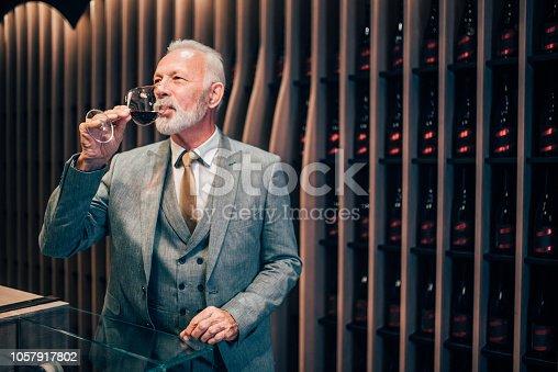Senior male sommelier drinking red wine