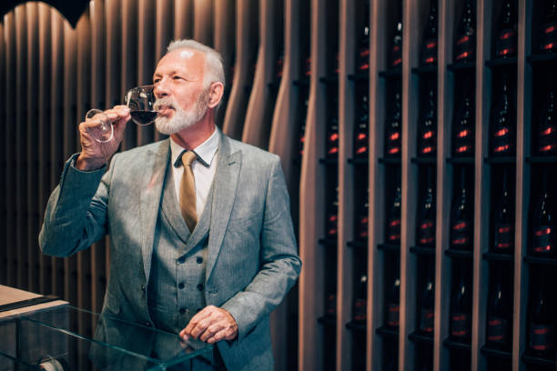 Old man tasting red wine Senior male sommelier drinking red wine upper class stock pictures, royalty-free photos & images