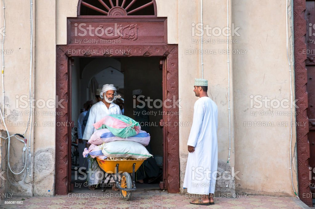 old man transporting goods in a wheelbarrow at a market stock photo