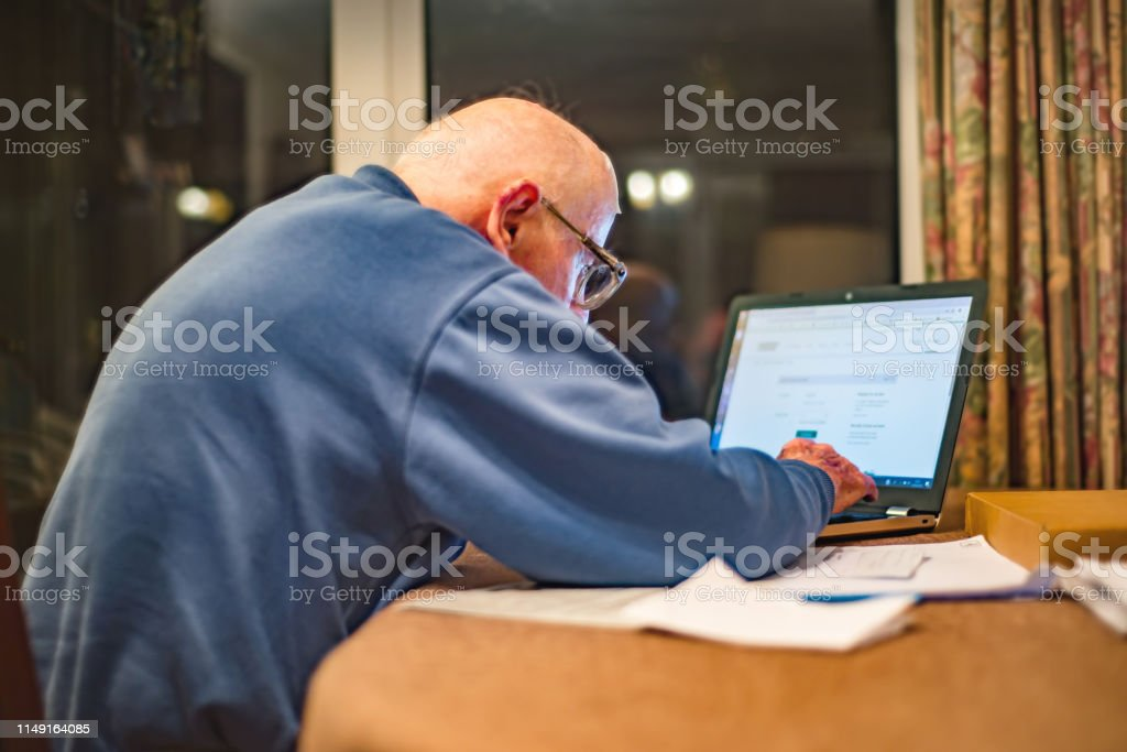 Elderly man of 93 years having trouble using his computer to check...