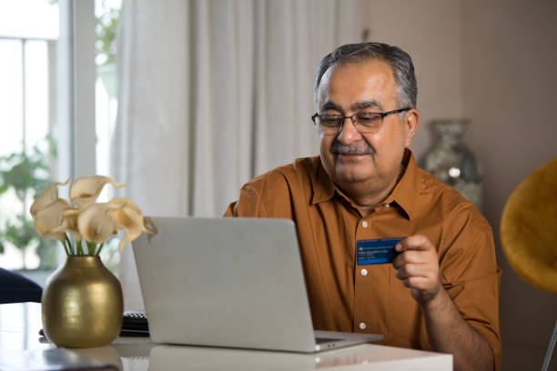 Old man using laptop and credit card at home stock photo