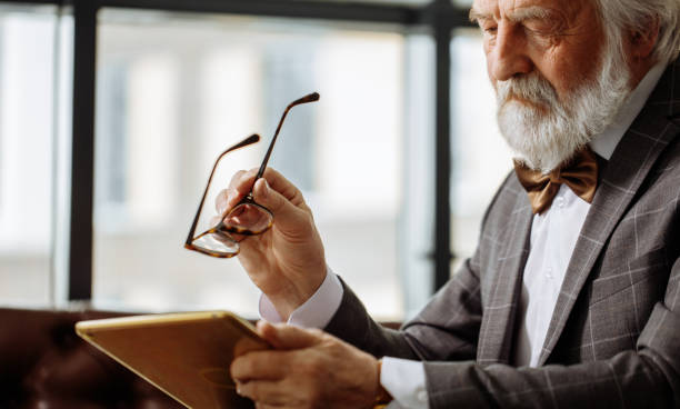 old man with bad eyesight trying to descry an image on the screen of the tablet old man with bad eyesight trying to descry an image on the screen of the tablet. old man with poor eyesight. descry stock pictures, royalty-free photos & images
