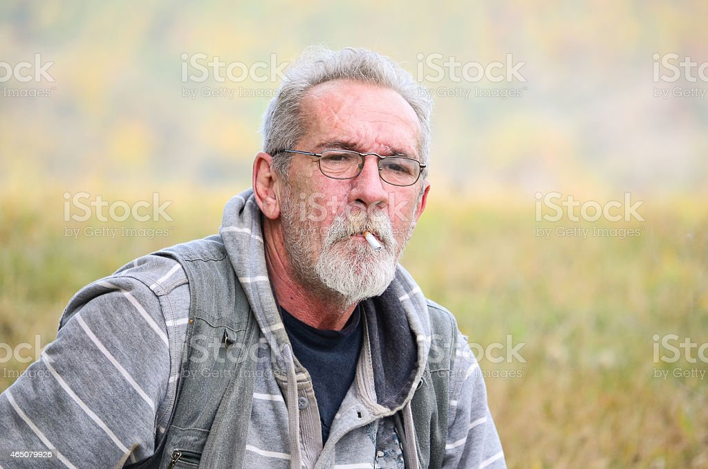 Old man with cigarette stock photo