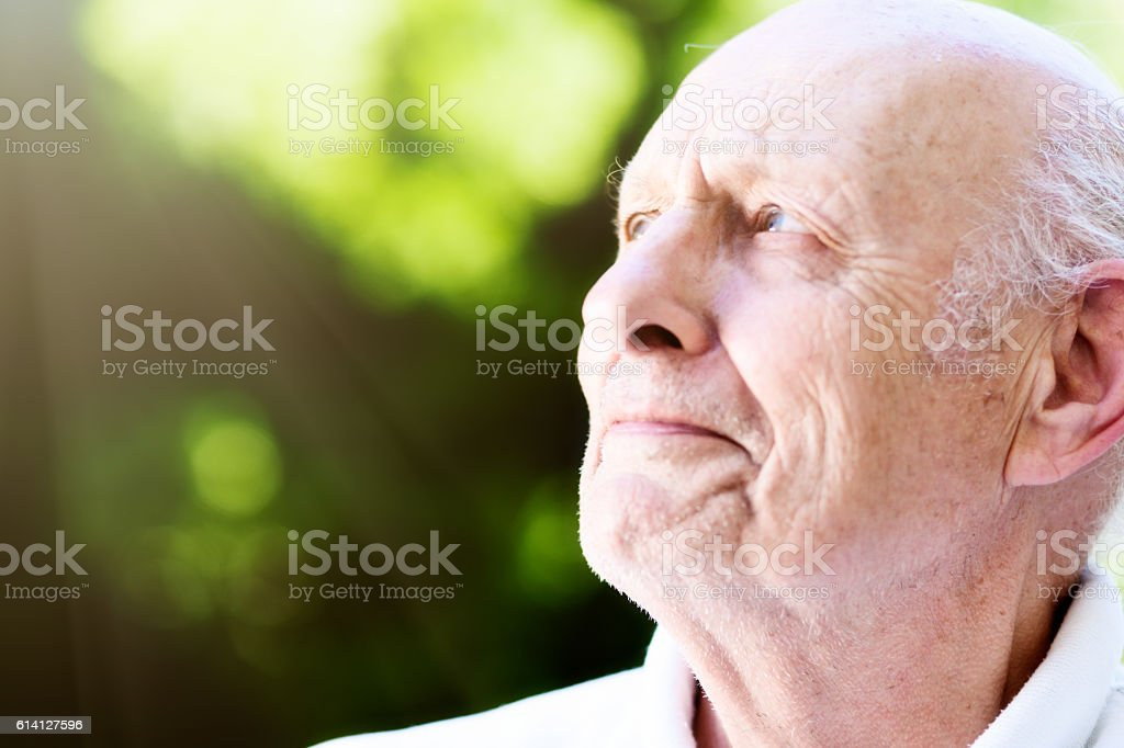 Old man with eye trouble squints up at sun stock photo
