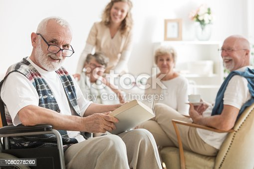 istock Old man with glasses sitting on wheelchair reading a book 1080278260