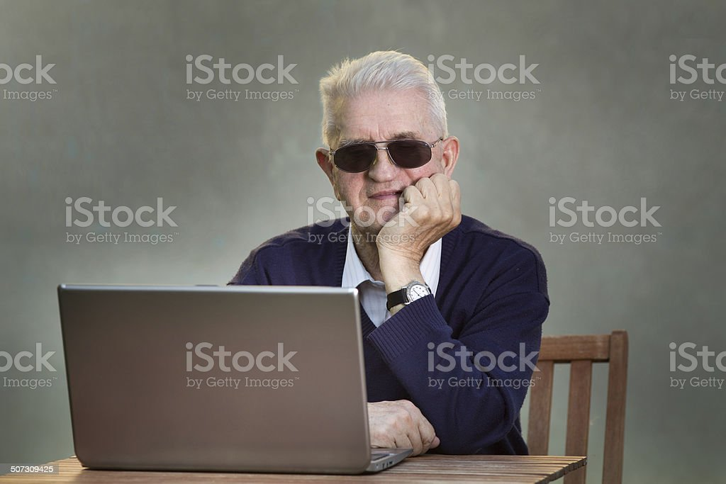Old man with laptop stock photo
