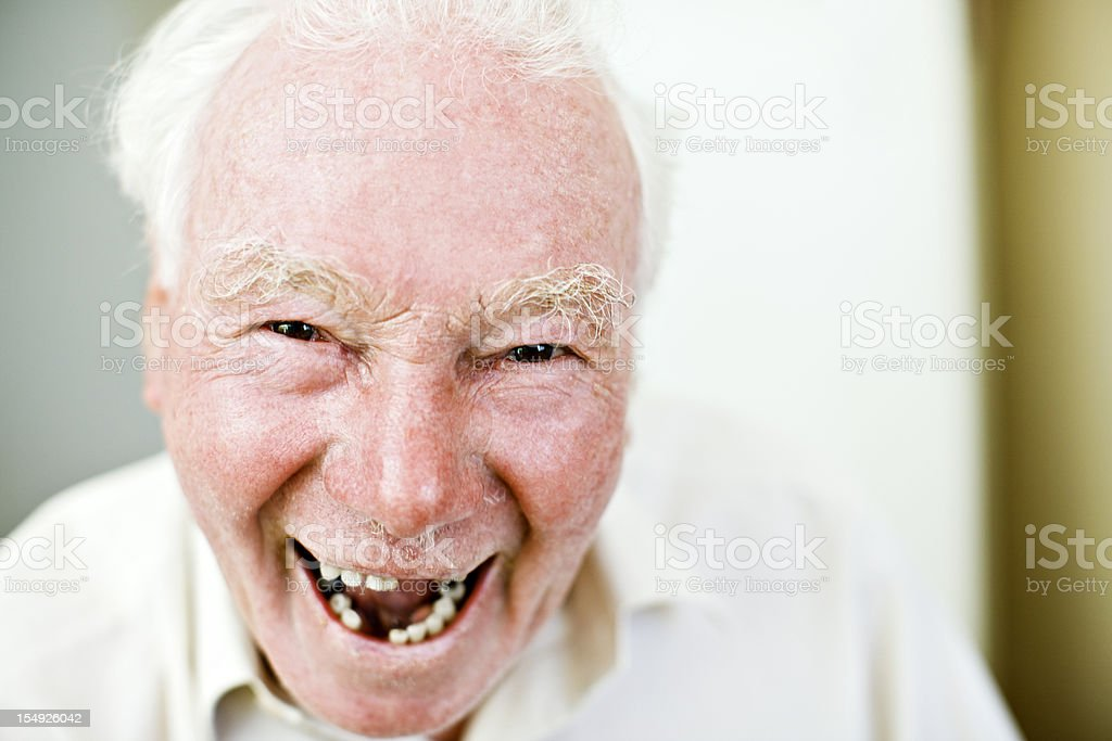 Old man with missing teeth smiles happily stock photo