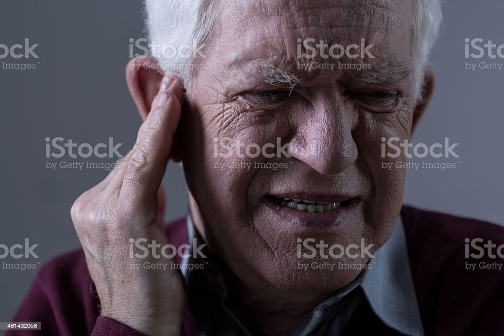 Old man with tinnitus stock photo