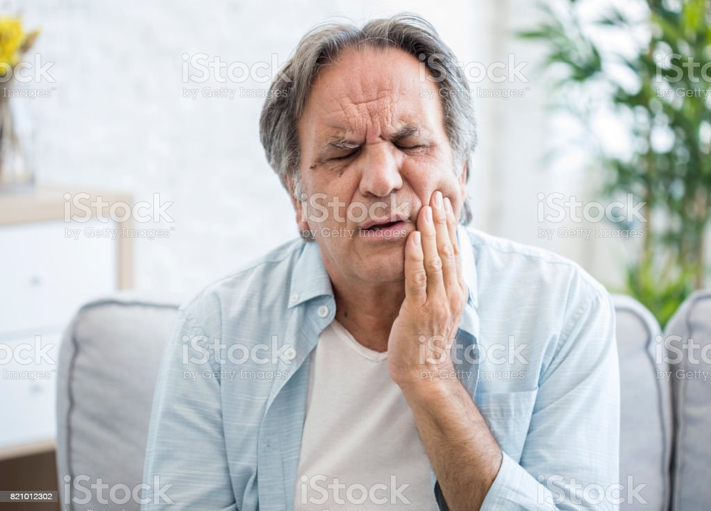Old man with tooth sensitivity stock photo