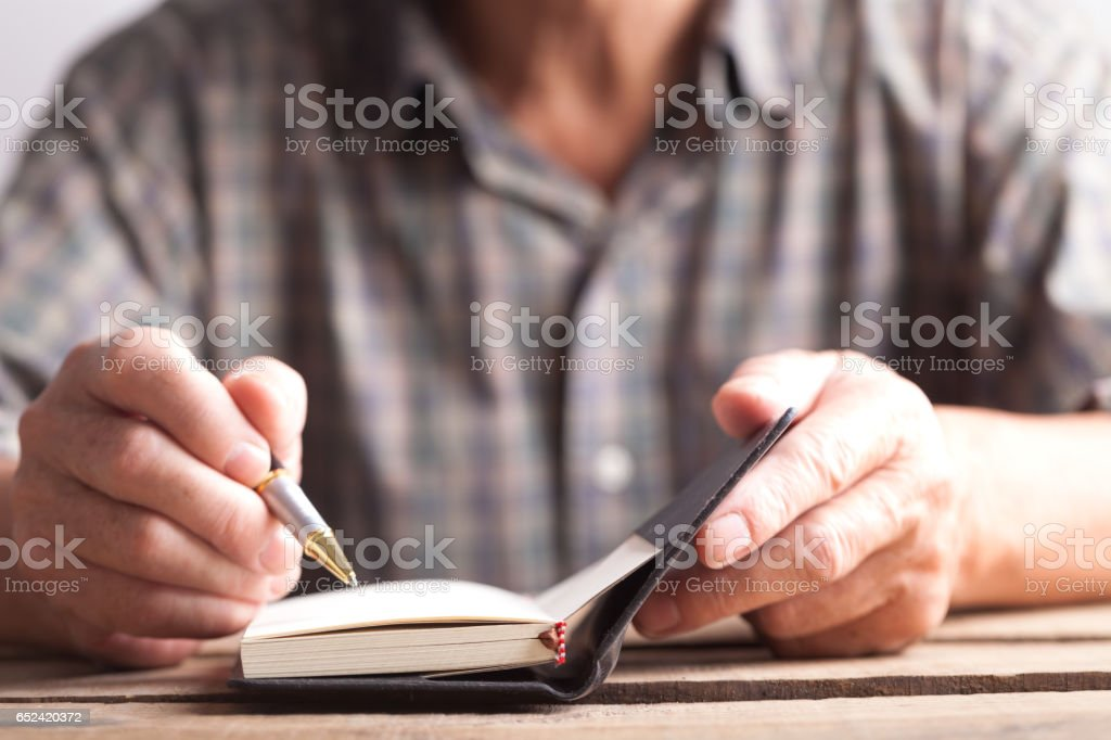 old man writing notes in book stock photo
