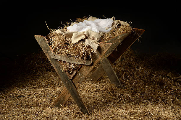 Old Manger with Soft Clothes Old manger with old clothes as a symbol of waiting for Christmas trough stock pictures, royalty-free photos & images