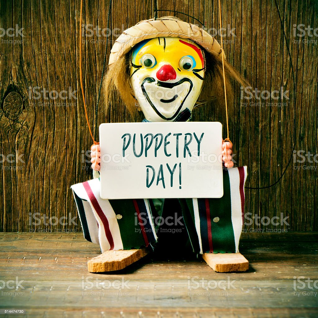 old marionette with a signboard with the text puppetry day stock photo