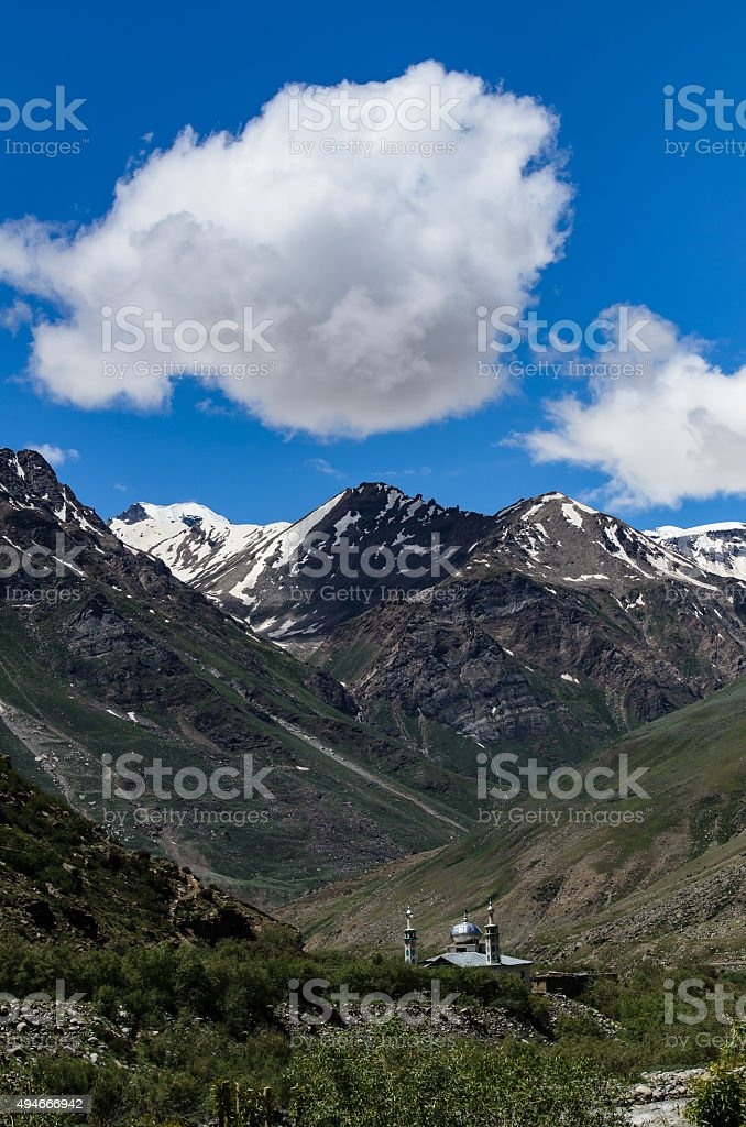 Old Masjid with sunny day with snow mountain background, Kashmir stock photo