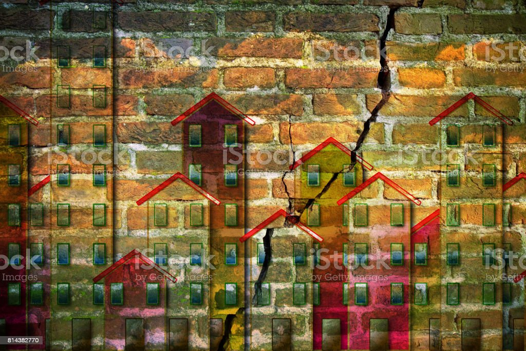 Old masonry buildings which need of a seismic improvement - concept image with buildings against a cracked brick wall stock photo
