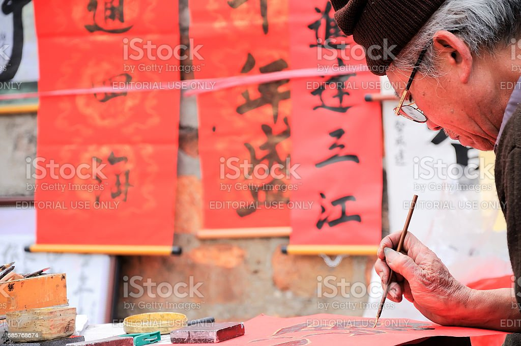 Old master writing ancient letter at new year, Hanoi, Vietnam stock photo