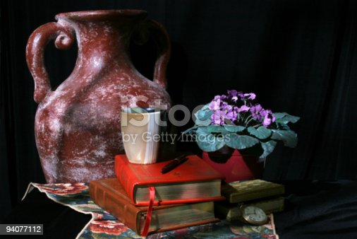 Still life to appear as light is coming from the window.  Collection of an earthern jug, leather bound books, coffee mug, aftican violets in pot, treasure box and old pocket watch on black background with a tapestry runner.