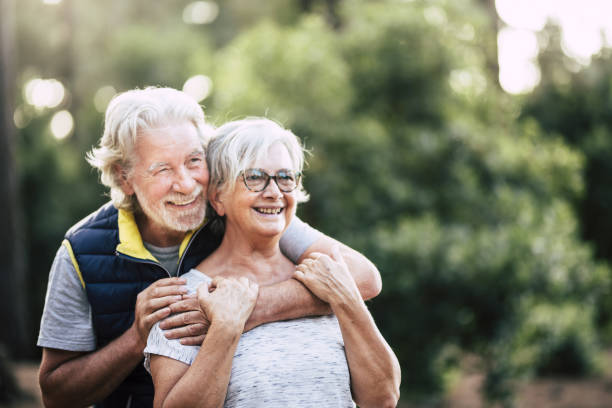 Old mature retired senior people smile and enjoy the love couple during outdoor leisure activity together - green forest and wood in background for environment concept stock photo