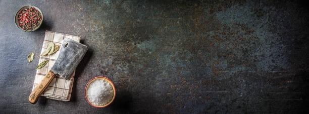 Altes Fleisch Metzgerei auf dunklen Betonplatte mit Gewürzen, Salz und Pfeffer. – Foto