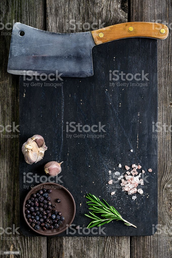Old meat cleaver on wooden cutting board stock photo