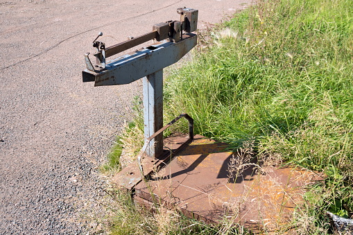 Old mechanical goods scales stand on the grass, on the side of the road, in summer