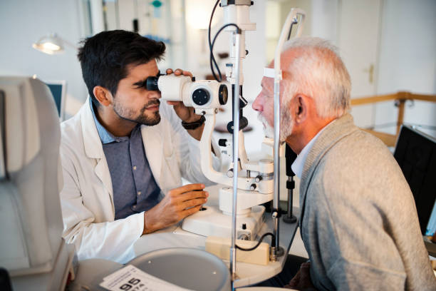 Old men having an eye exam at ophthalmologist's office. stock photo
