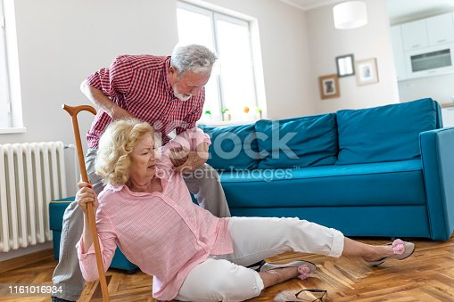 retired husband coming to upset senior wife sitting on floor with walking cane.senior men helping at old woman who falled down on floor