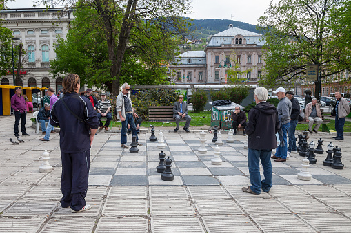 Old men playing a giant chess game in the city center of Sarajevo, capital city of Bosnia. This chess game is one of the symbols of the life in the city