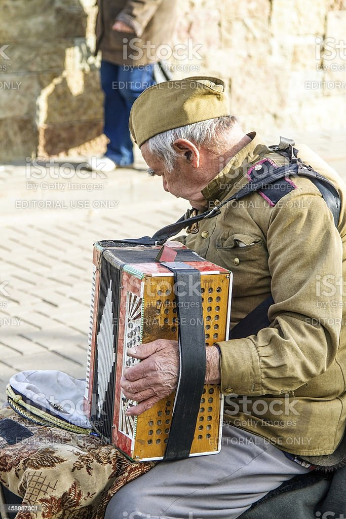 Old men playing the accordion on city street royalty-free stock photo