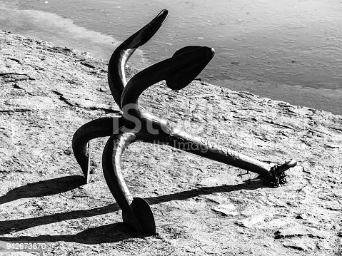 501889762istockphoto Old metal anchor on the land. Black and white image 942673670