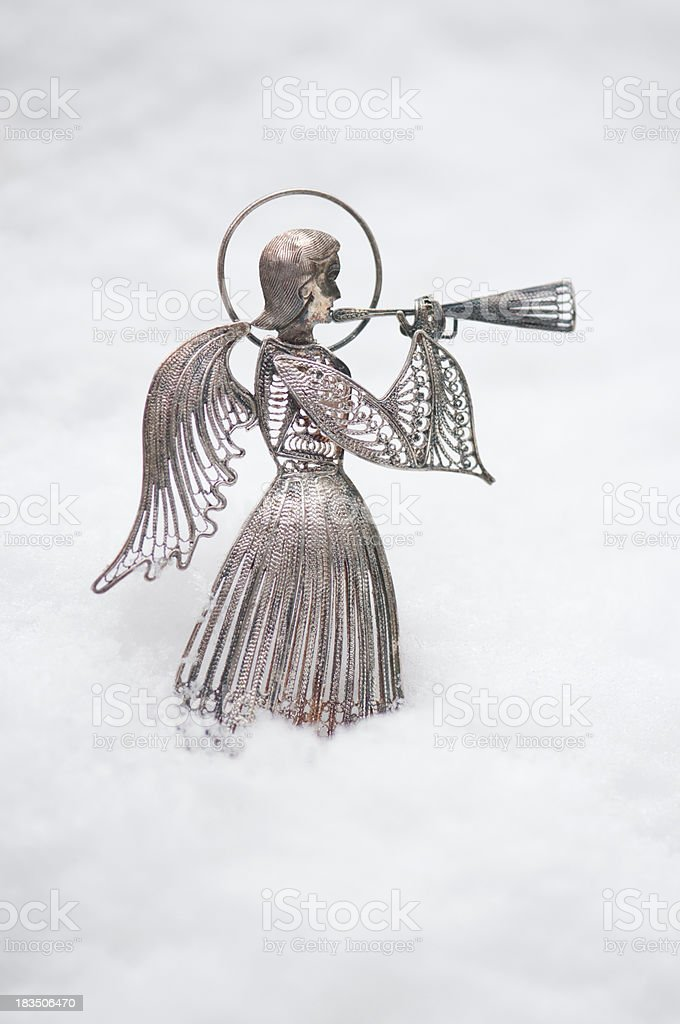 Old metal angel ornament outside in real snow royalty-free stock photo