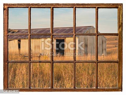 old metal barn in Nebraska Sandhills as seen from a vintage sash window