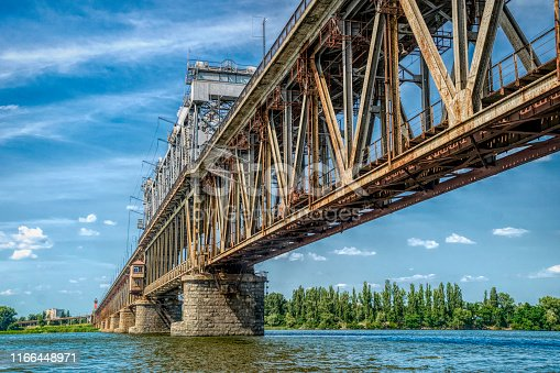 Old rusty bridge over the Dnieper River in the city of Kremenchug, Ukraine. Old architecture of Eastern Europe
