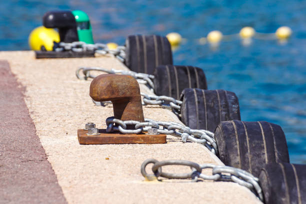 Old metal dock mooring pole with ring and rope for securing fishing boats Old metal dock mooring pole with ring and rope for securing fishing boats . amortize stock pictures, royalty-free photos & images