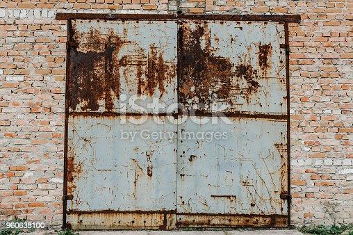 istock Old metal door from the garage. Rusty. Garage old red bricks. Barn. Gray garage door in an old house. 960638100