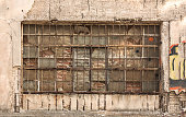 Old metal glass squared industrial window, blacked with red bricks from inside.