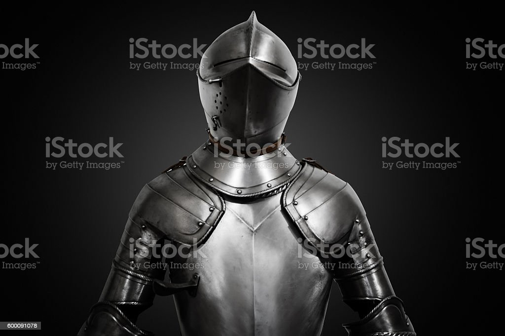 Old metal knight armour on black background stock photo