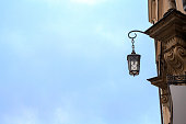 Old metal lantern hanging on building by blue sky background. Vintage lamp on house wall with copy space