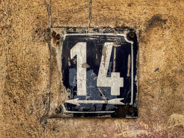 Old metal plate with number 14 stained with facade paint placed on an old brick wall stock photo