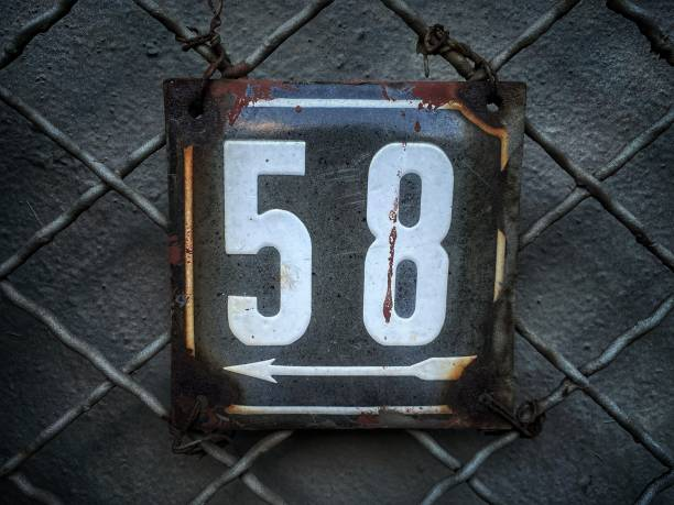 Old metal plate with number 58 hung on a wire fence. stock photo