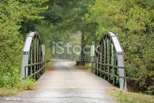 Looking down long road across old steel truss bridge