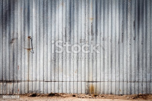 Old rusty metal warehouse wall. Architecture detail background. Metal steel texture surface of cargo wall