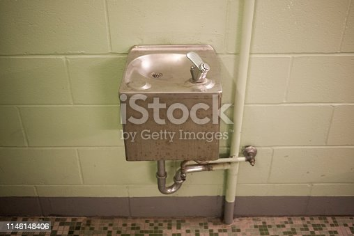 Vintage metal water fountain in a public school changing room.