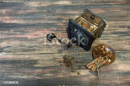 Old metallic copper coffee grinder on the wooden table background