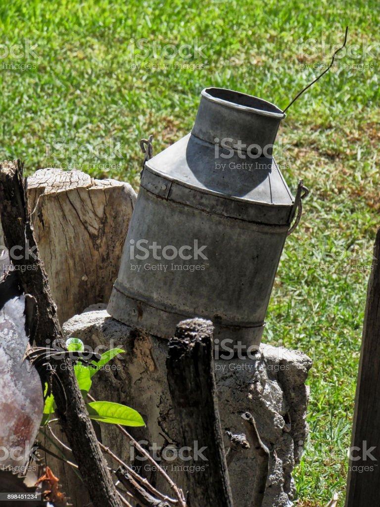 Old Metallic Milk Bucket in Backyard as Garden Decoration stock photo
